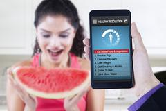 Healthy resolutions app with woman eats watermelon Stock Photos