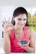 Model with blueberry shows OK sign Stock Photos