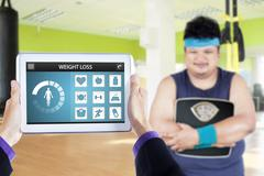 Obese man with scale and app of weight loss - stock photo