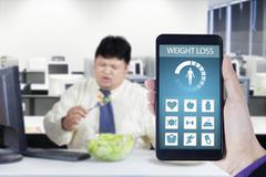 Overweight worker and weight loss app - stock photo