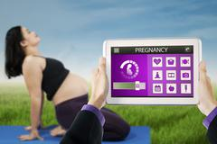 Pregnant woman doing yoga with pregnancy app - stock photo