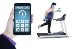 Weight loss app and man exercising on treadmill Stock Photos
