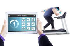 Weight loss app and man runs on treadmill - stock photo