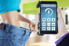 Woman with old jeans and weight loss apps - stock photo