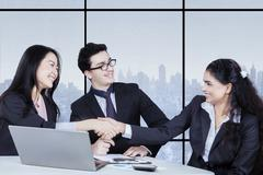 Workers closing a deal and shaking hands - stock photo