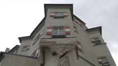Low angle view of an old building with red and white shutters in Innsbruck Stock Footage