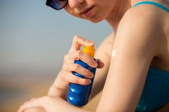 Spraying sunscreen lotion on shoulder Stock Photos