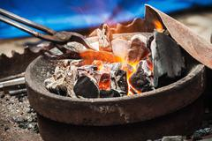 forge a burning forge and tools - stock photo