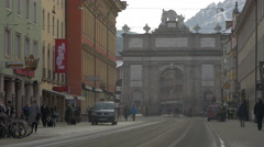 People walking and cars driving close to Triumphforte in Innsbruck Stock Footage