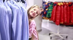 Baby girl looking at clothes in fashionable shop Stock Footage