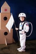 Beautiful preschool boy, dressed as astronaut, with flag and carton rocket Stock Photos