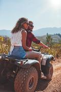 Young couple enjoying a quad bike ride in countryside Stock Photos