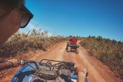 Young people driving quad bikes - stock photo