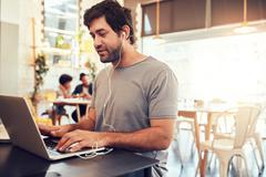 Young guy at a cafe surfing internet on laptop - stock photo