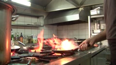 Seafood restaurant kitchen, chef fries calimari over hot stove flame Stock Footage