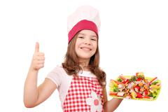 happy little girl cook with seafood and thumb up - stock photo