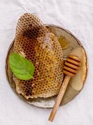 Honeycomb in ceramic plate with peppermint and dipper on white fabric backgro Stock Photos