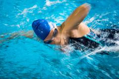 Female swimmer in an indoor swimming pool - doing crawl (shallow DOF) Stock Photos