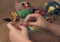 Children's hands are weaving figures out colored rubbers Stock Photos