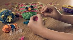 children's hands are weaving figures out colored rubbers - stock photo