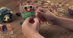 hands are weaving figures out colored rubbers - stock photo