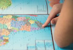 Young tourist couple looking world map will travel - stock photo