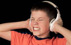 teenager boy in headphones with loud music scared - stock photo