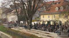 Crowded area on the riverside of Ljubljanica River in Ljubljana Stock Footage