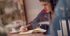 Young Woman Writing Journal at Window Seat in Coffee Shop - stock footage