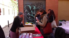 Spanish people in small queue, woman give ticket and take roasted roots, Stock Footage