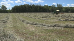Haying square bales with a tractor and trailer. Stock Footage