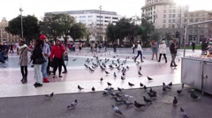 People walk at Catalonia Square, many dove birds on ground, cool february - stock footage