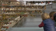 Boy playing at the railing on the Butchers' Bridge in Ljubljana Stock Footage