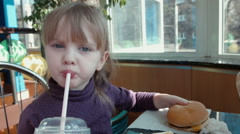 The little girl drinks cocktail Stock Footage