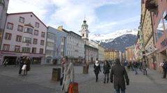 People walking on Maria-Theresien-Strasse close to Spitalskirche, Innsbruck Stock Footage