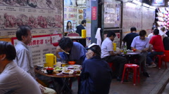 Stock Video Footage of Hong Kong China Kowloon Woosung Street locals eating chinese food on the street