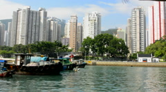 Hong Kong China Aberdeen from boat in water of reclaimed land with skyscraper Stock Footage