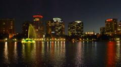 Orlando Florida Lake Eola skyline twilight night colored lights statue night Stock Footage