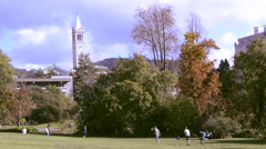 University of California at Berkeley with student on laptop while others play Stock Footage