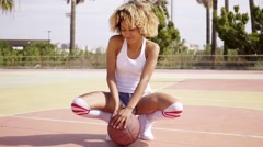 Young black female athlete sits with in ball court - stock footage
