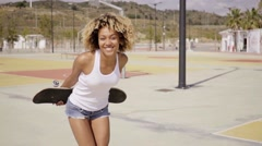 Pretty female skater holds board behind her Stock Footage