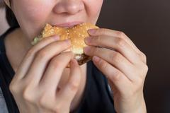 Asian girl eat hamburger Stock Photos