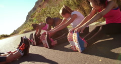 Multi-ethnic group of athletes doing hamstring stretch exercise outside - stock footage