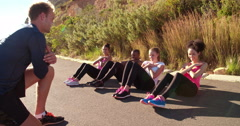 Group of young adult athletes doing sit-ups outside Stock Footage