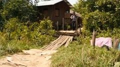 Tourist backpacker on a small bridge in Myanmar village Stock Footage