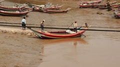 Local passengers with ambrellas go to the small boat - Myanmar Stock Footage