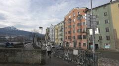 Woman crossing the Innerstrasse street in Innsbruck Stock Footage