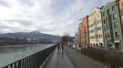 Walking and riding bikes by Inn riverside in Innsbruck Stock Footage