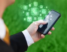 Hand holding smartphone with mobile app icons - stock photo