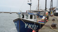 Fishing Boats Moored In Harbour While Fisherman Land The Catch UK Norfolk Coast Stock Footage